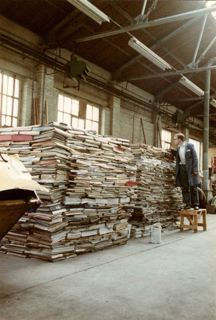Records management rescue of shipyard records. Piles of records wwhich are being accessed by a person on a step