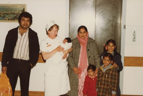Archival photo. A family of Punjabi descent stand by a hospital lift with an older white woman, who holds a newborn baby in her arms.