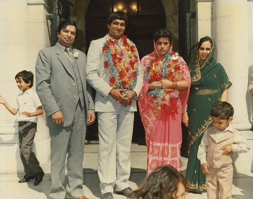 Archival photo. A family group of Pubjabi descent stands outside a sandstone building. In the centre, the bride and groom wear traditional silk flower garlands.