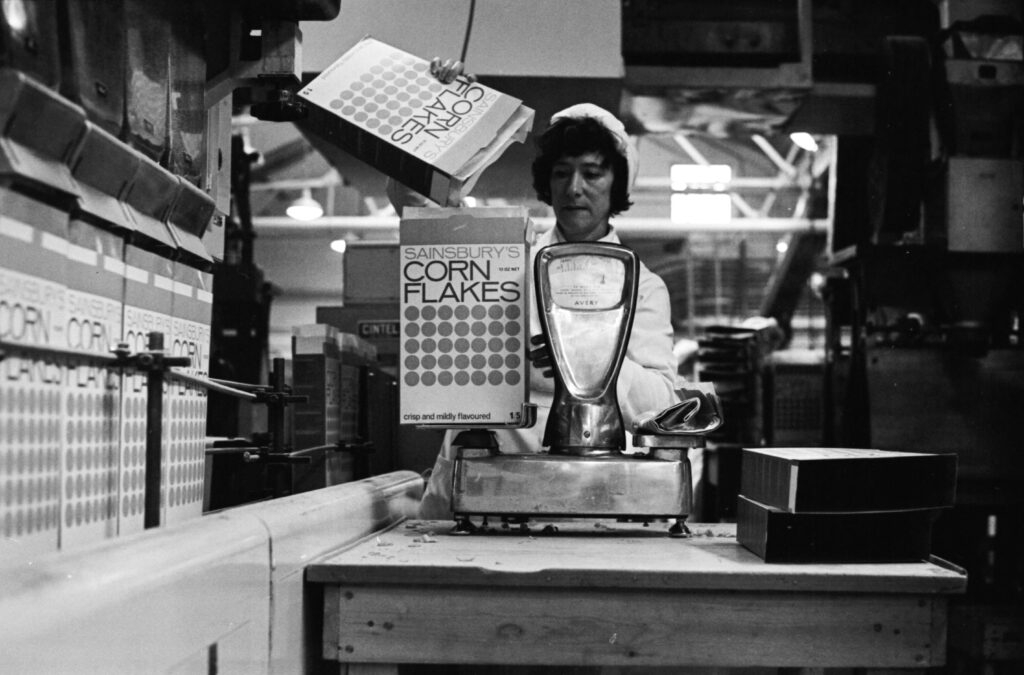 Black and white image, c.1968, of a woman in a white factory coat and hat, weighing corn flakes into a Sainsbury's branded box.