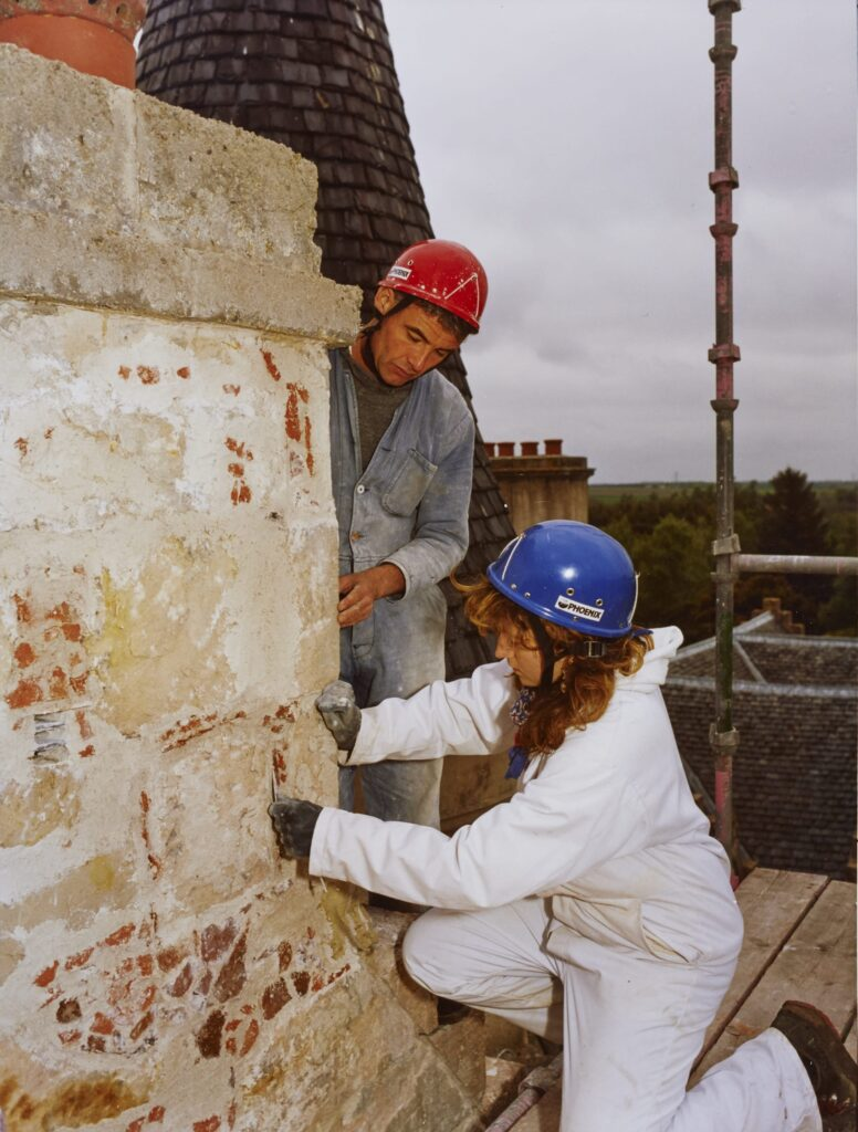 Two workers in hard hats and protective clothing work on a crumbling wall.