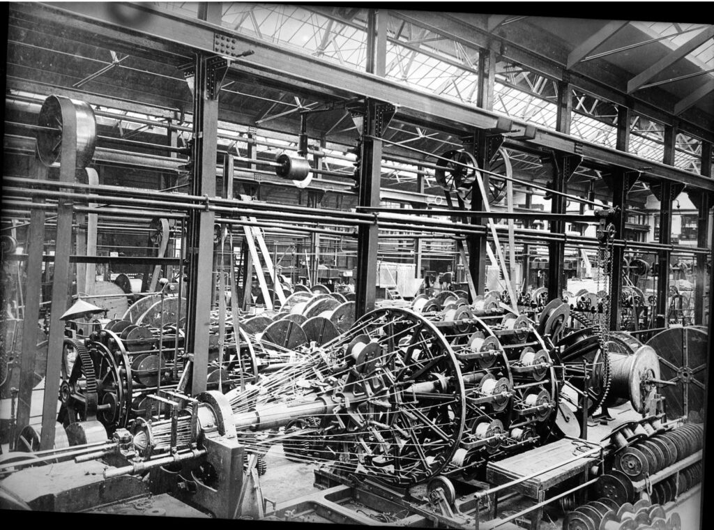 Black and white image of 1930s production line. Multiple spools of thread are twisted together by a stranding machine.