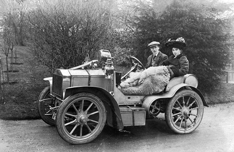 Black and white early twentieth-century image of a couple in a vehicle.