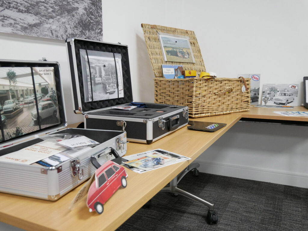 Image of three cases on a table. One case is a wicker picnic basket style. The other two are metal briefcases. The boxes contain leaflets, badges, and other archival items. One box has been labelled 'The Art of Selling'.
