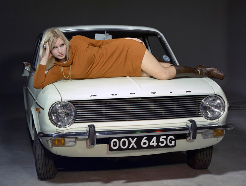 Colour image of an Austin Maxi car with a woman reclining on the bonnet.