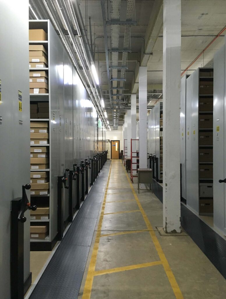 Colour image of archive stores. There are numerous metal shelving units on roller wheels and yellow guide lines on the floor.