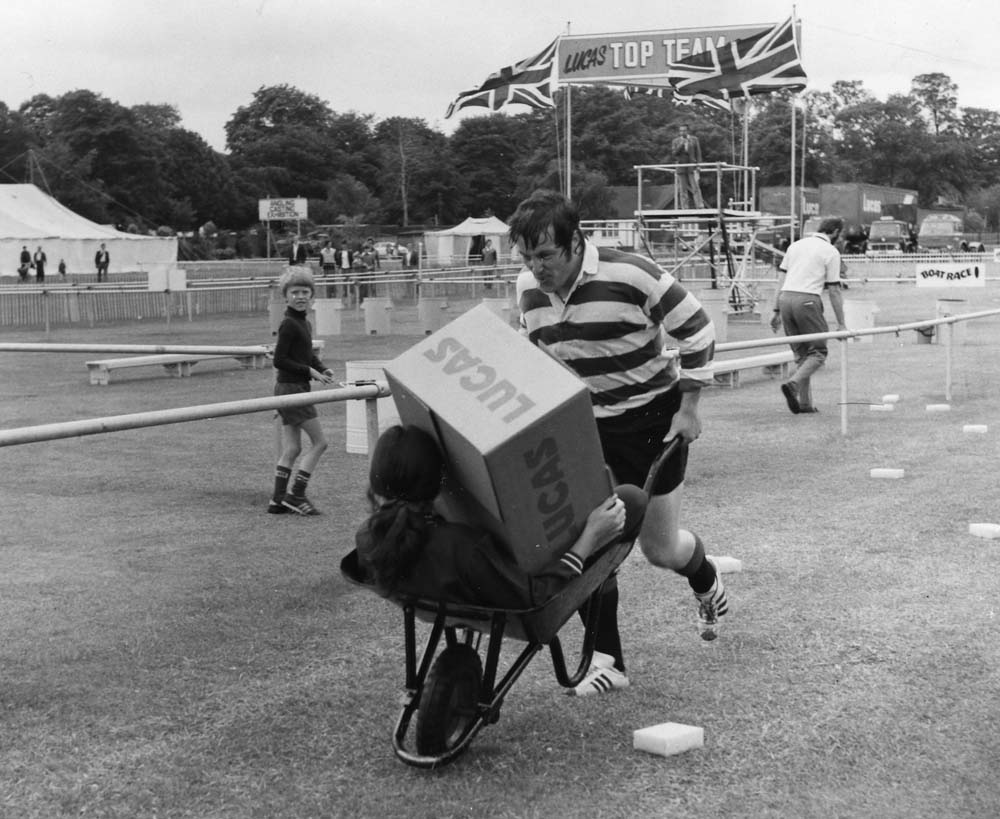 Black and white image of a man in sporting clothes running while pushing a wheelbarrow. A girl sits in the wheelbarrow holding a cardboard box with 'LUCAS' printed on the side. A young boy looks at the camera.