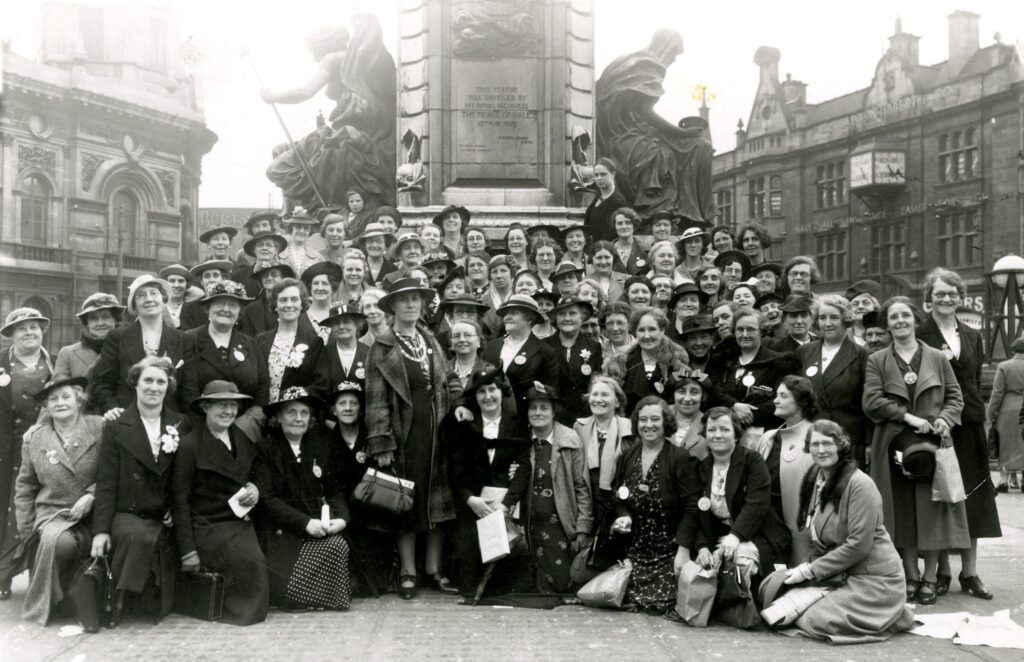 Black and white image of a group of women in 1930s dress grouped around a statue.